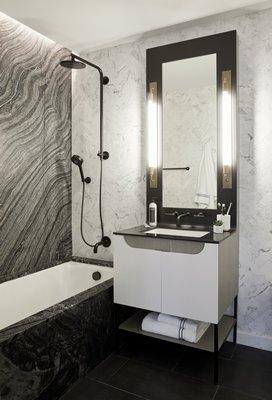 An elongated custom vanity mirror in a luxurious stone bathroom. CHRISTIAN HARDER