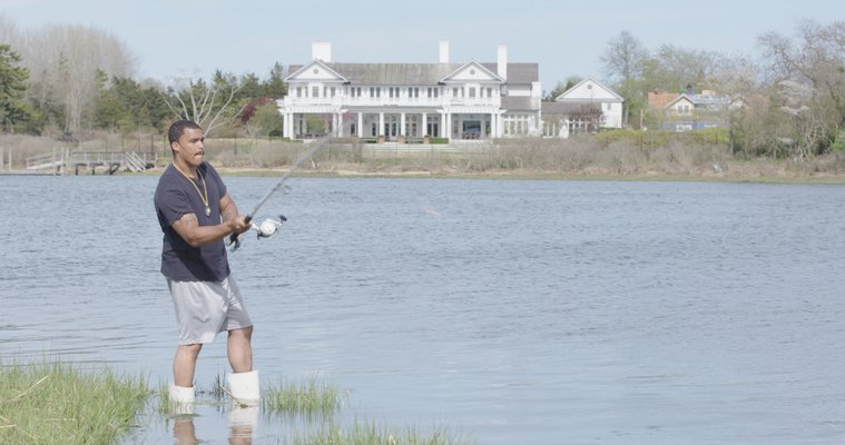 Shane Weeks, a member of the Shinnecock Indian Nation, fishes on the reservation in Southampton across from luxury homes.