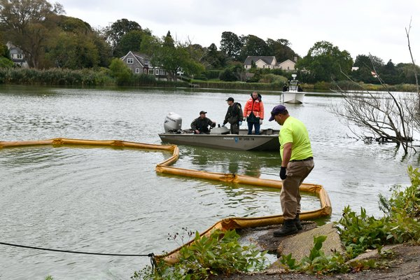Crews position containment booms in Lake Agawam on Thursday morning.    DANA SHAW