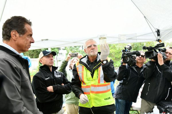David Pinelli, left, senior scientist from Aecom, demostrates how the portable water treatment system works.   DANA SHAW
