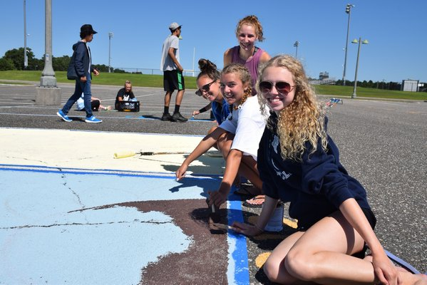 Students gather around their mural in the parking lot.