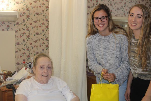 Arline Waterburg smiles as she is surprised by Allyson and Siobhan with her gift bag.