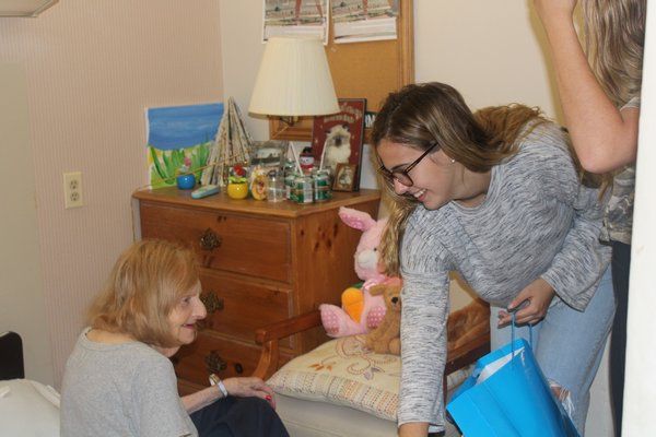 Allyson hands resident Helen Vermont a gift bag with a dog stuffed animal to add to her collection.