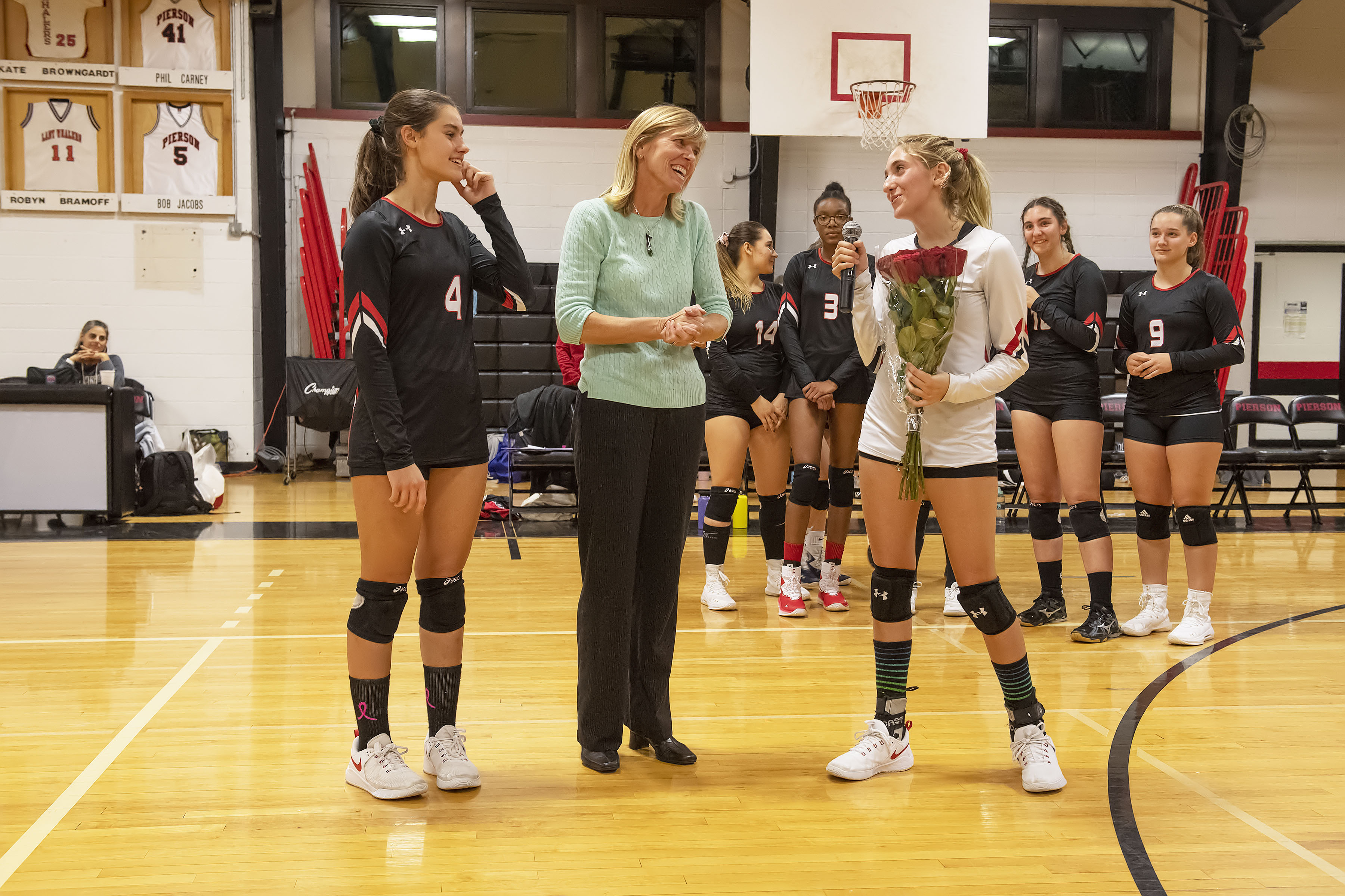 Pierson seniors Samantha Cox, far left, and Olivia Cassone honored their coach, Donna Fischer, during a pregame Senior Day ceremony before the Lady Whalers hosted Babylon on Monday night.