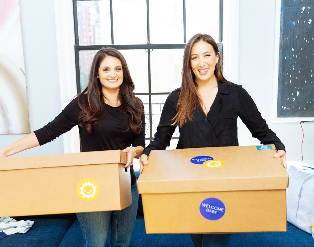 Welcome Baby co-founders, Juliet Fuisz and Sarah Steinhardt holding care packages containing all of the necessities for a newborn.   COURTESY CMEE