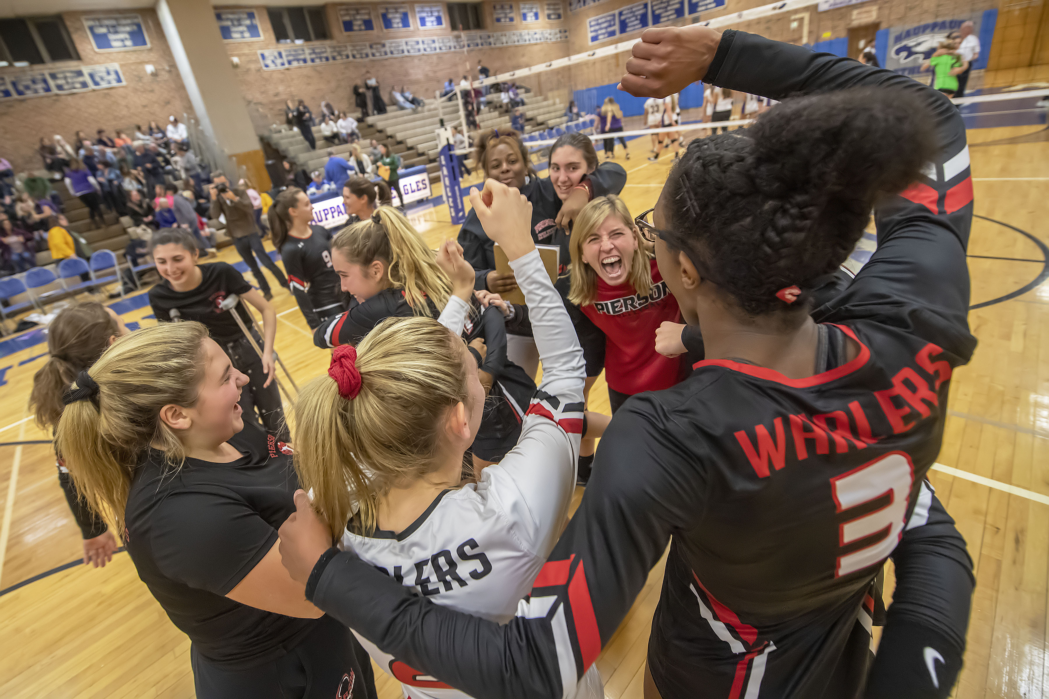 Pierson coach Donna Fisher, at center, celebrates with her team after the Lady Whalers defeated the Oyster Bay Lady Baymen to win the Long Island Class C Volleyball Championship at Hauppauge High School on Saturday night.