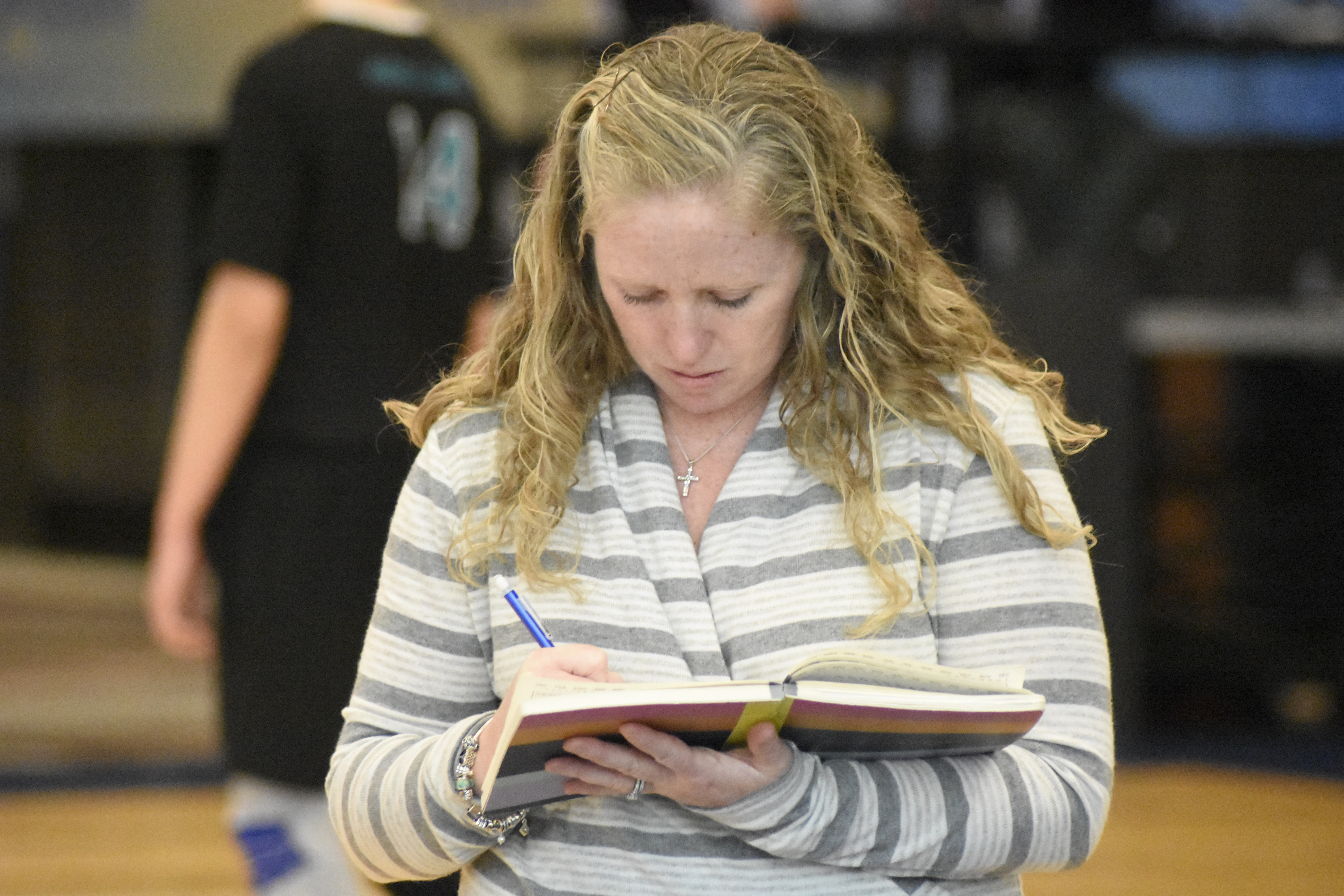 Westhampton Beach head coach Jackie Reed jots down a few notes in her book.