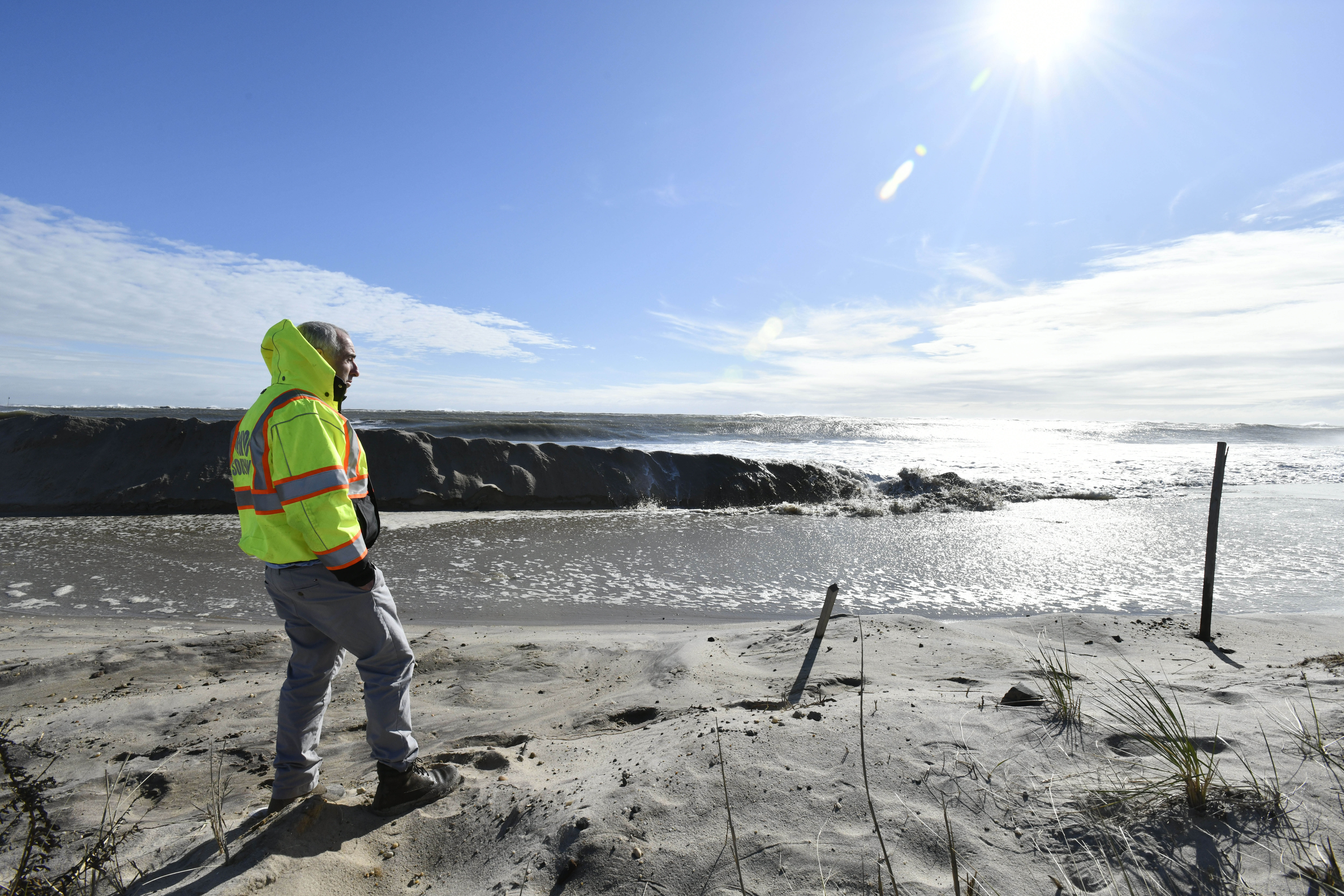 Southampton Town Supervisor Jay Schneiderman watches as the ocean washes away the dune across from the commercial fishing dock in Hampton Bays on Monday.  DANA SHAW