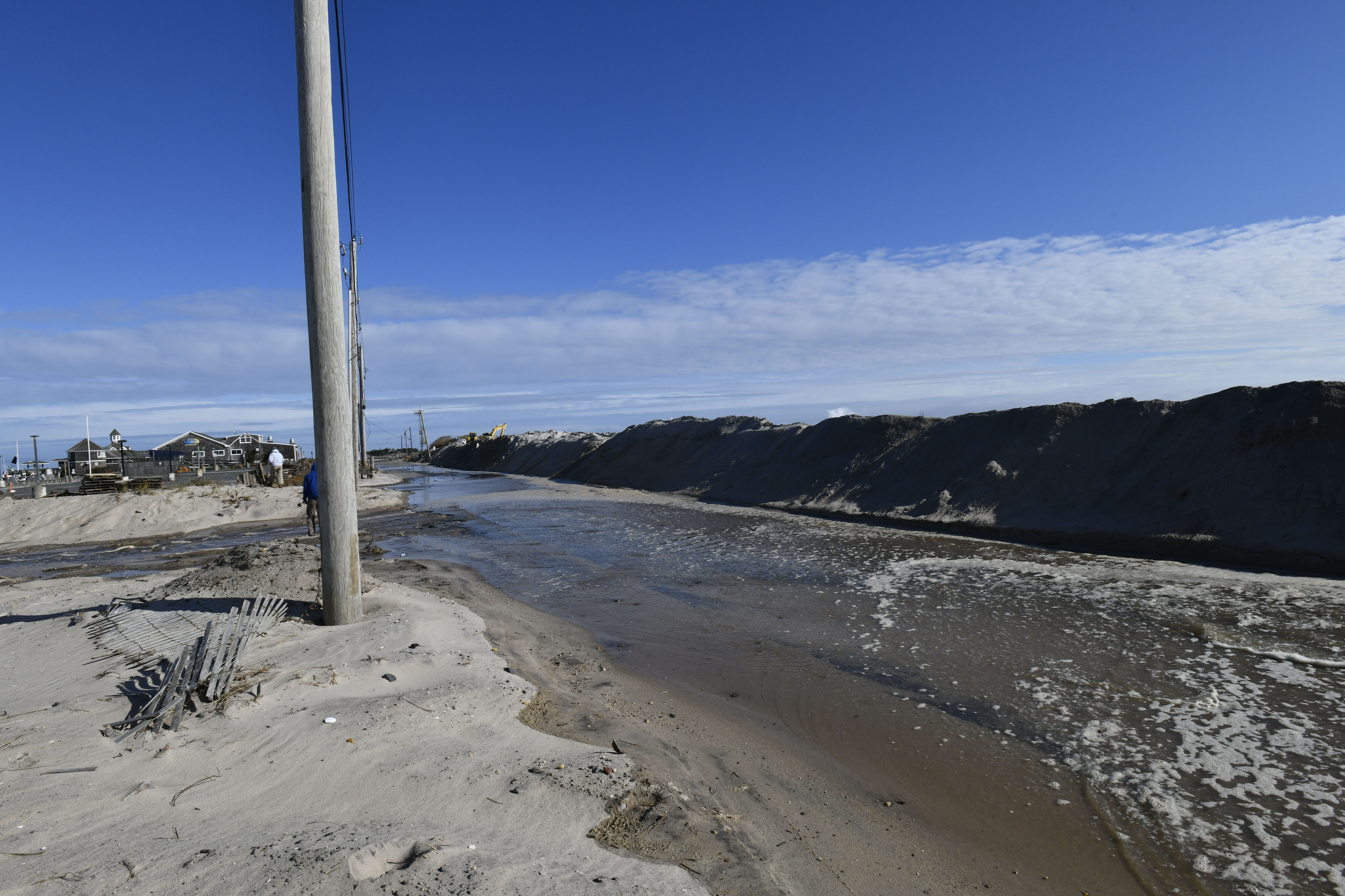 High seas wash away the dune across from the commercial fishing dock in Hampton Bays on Monday. DANA SHAW