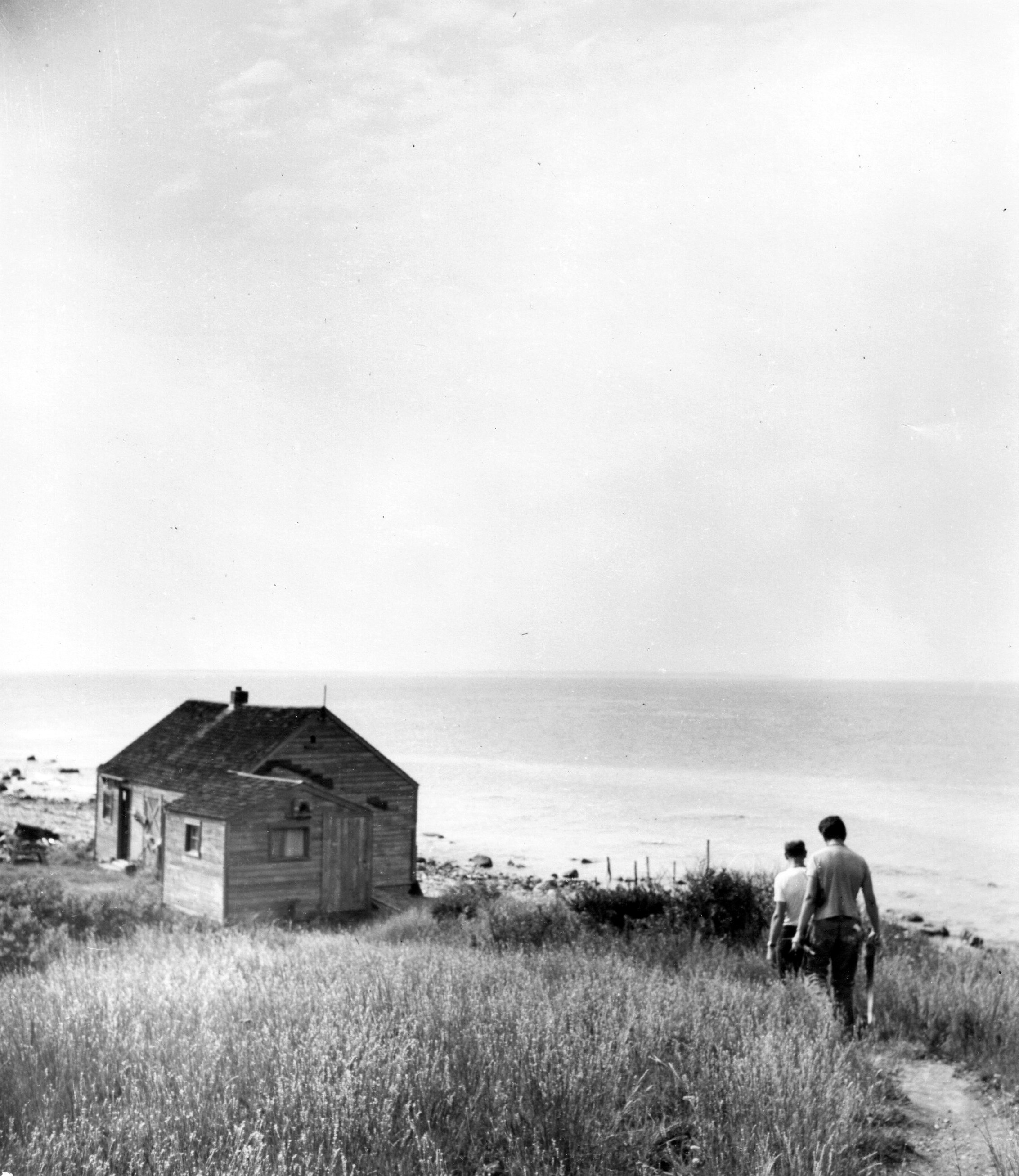 The small cottage that will be moved from the Brooks-Park property to the Pollock-Krasner House is pictured here when it was located on a bayside bluff in Montauk. The two men walking toward it in this photo, taken by Hans Namuth in 1950, are the artists James Brooks and Jackson Pollock.