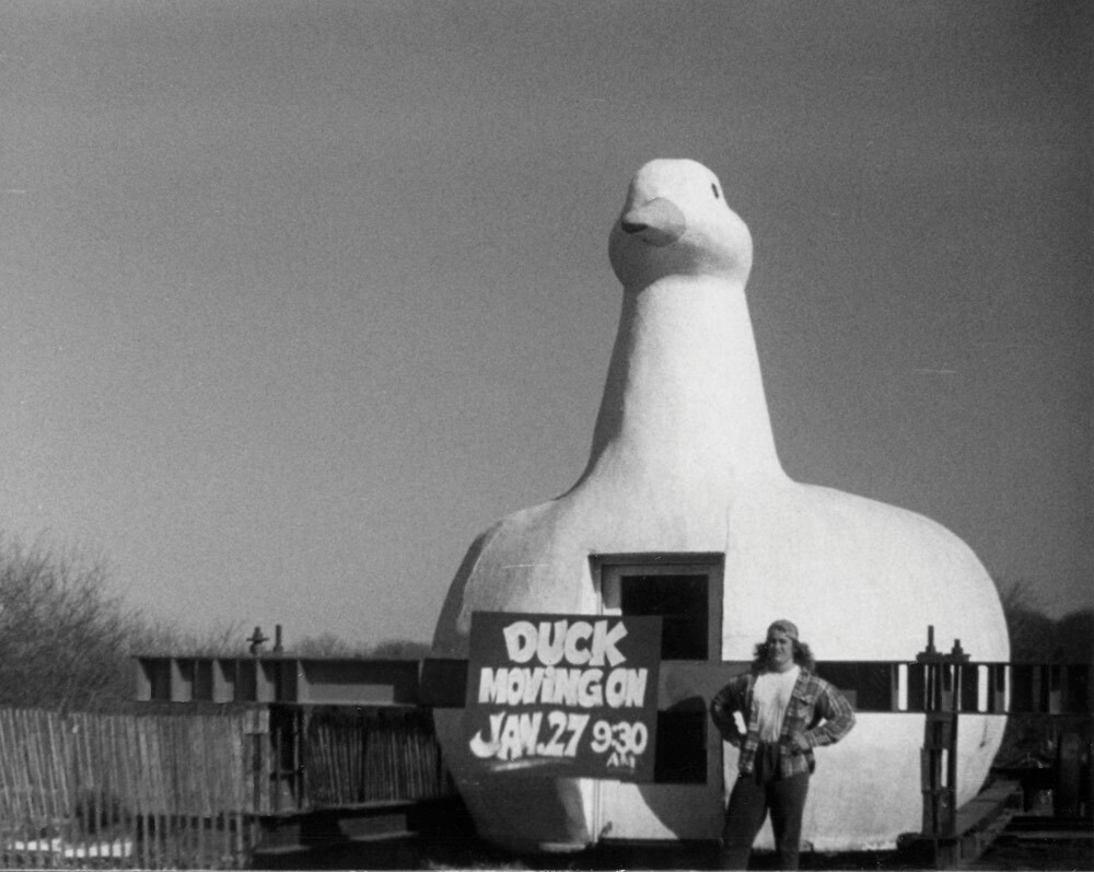 Dean Columbo next to sign announcing the relocation of the Big Duck, 1987 or 1988. COURTESY DEAN COLUMBO