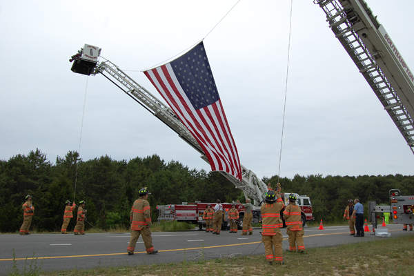 Southampton firefighters prepare the flag over County Road 39.<br></noscript>Photo by Brendan O'Reilly