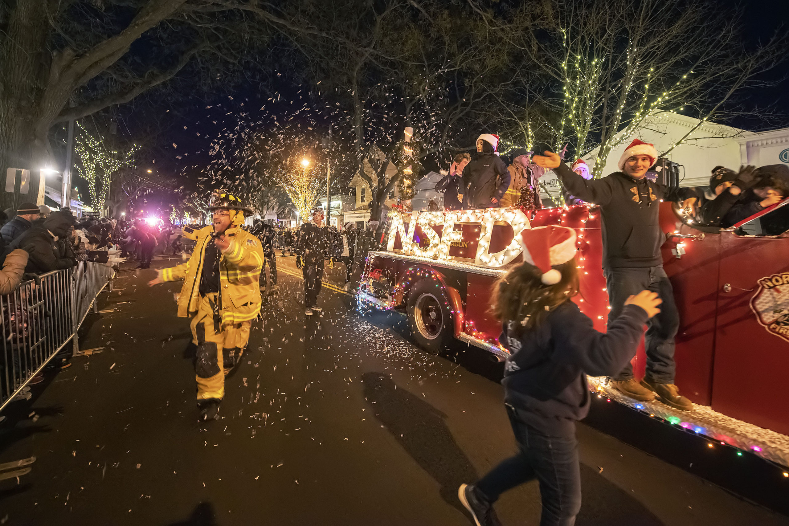 Members of the North Sea Fire Department Juniors throw confetti during the 2019 'Parade of Lights' in Southampton Village on Saturday night.