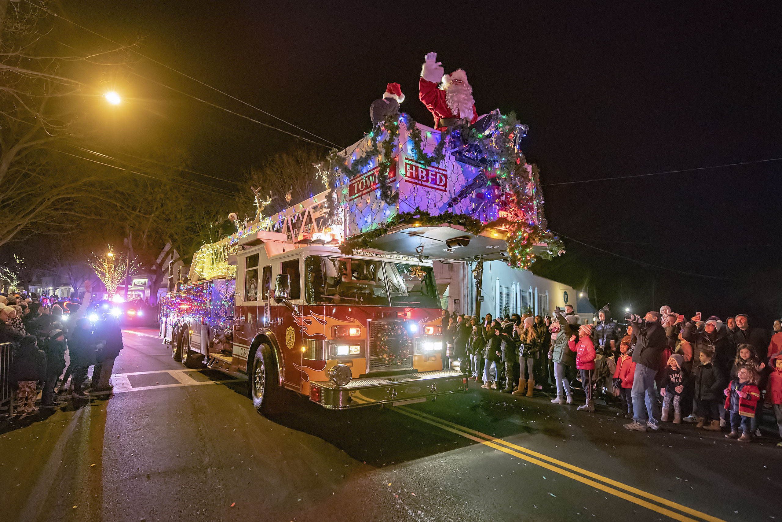 Santa Claus arrives on the parade route atop a Hampton Bays Fire Department tower ladder truck during the 2019