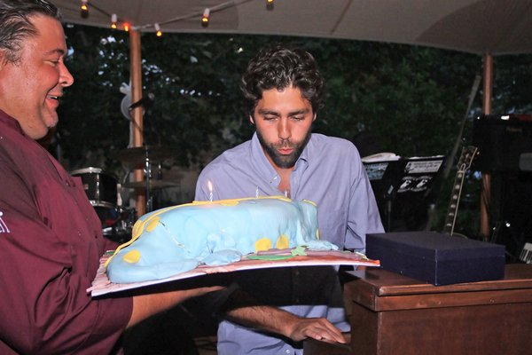 Adrian Grenier blows out the candles on his birthday cake.