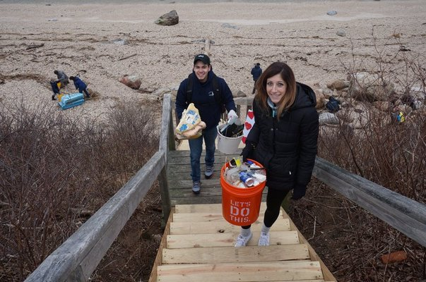 Volunteers carry debris from 67 Steps Beach in Greenport.. COURTESY ELI SURFRIDER FOUNDATION