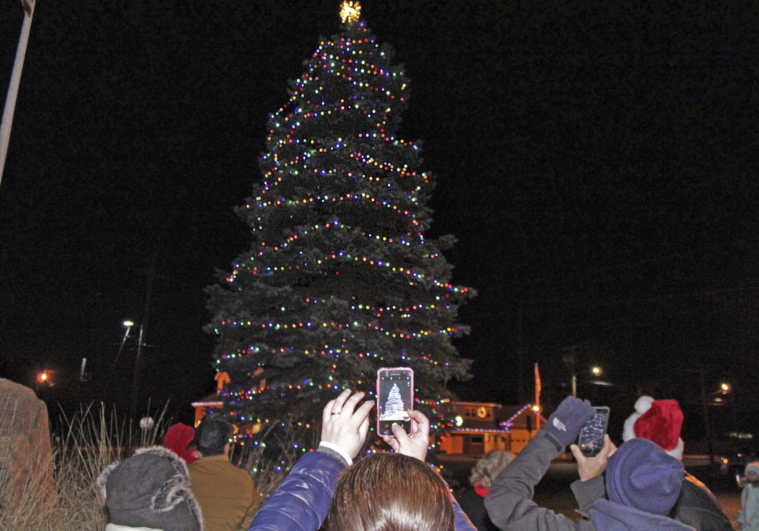 The crowd snaps photos as the tree is lit.