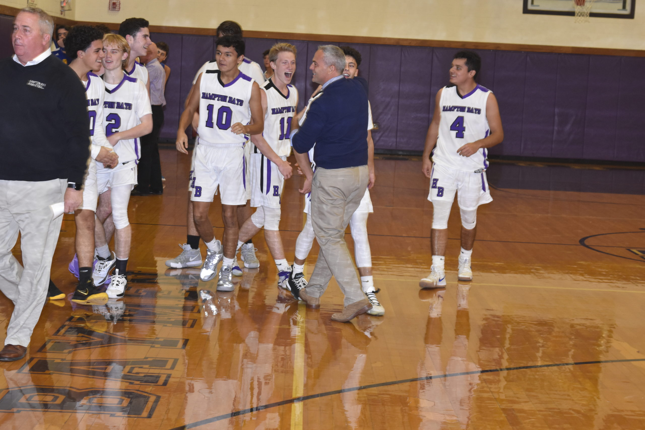Assistant coach John Paga and teammates congratulate Steven Mora after his half-court buzzer beater led to a 54-51 victory over West Islip on Friday night.