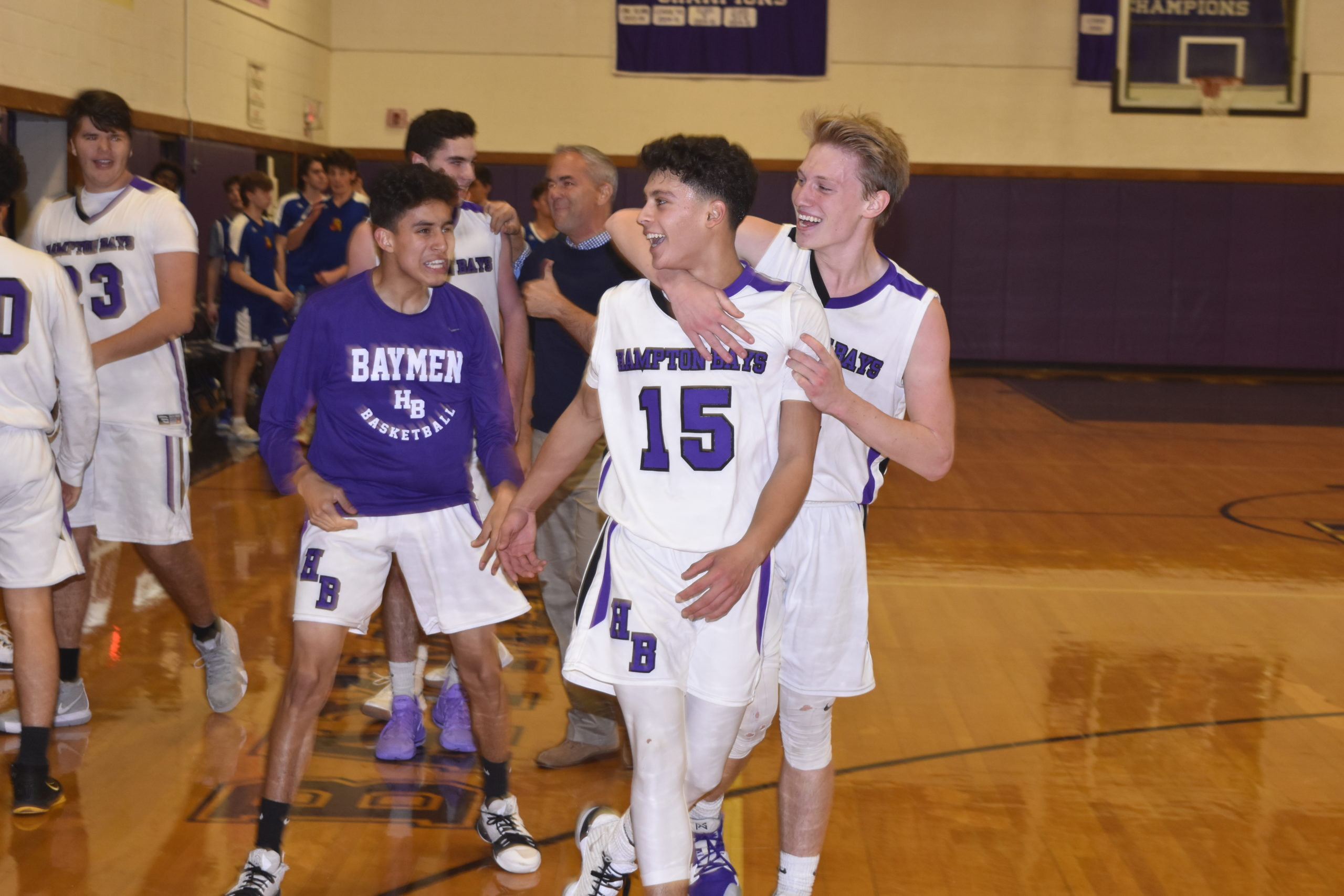 Lucas Brown and other teammates congratulate Steven Mora after his half-court buzzer beater led to a 54-51 victory over West Islip on Friday night.