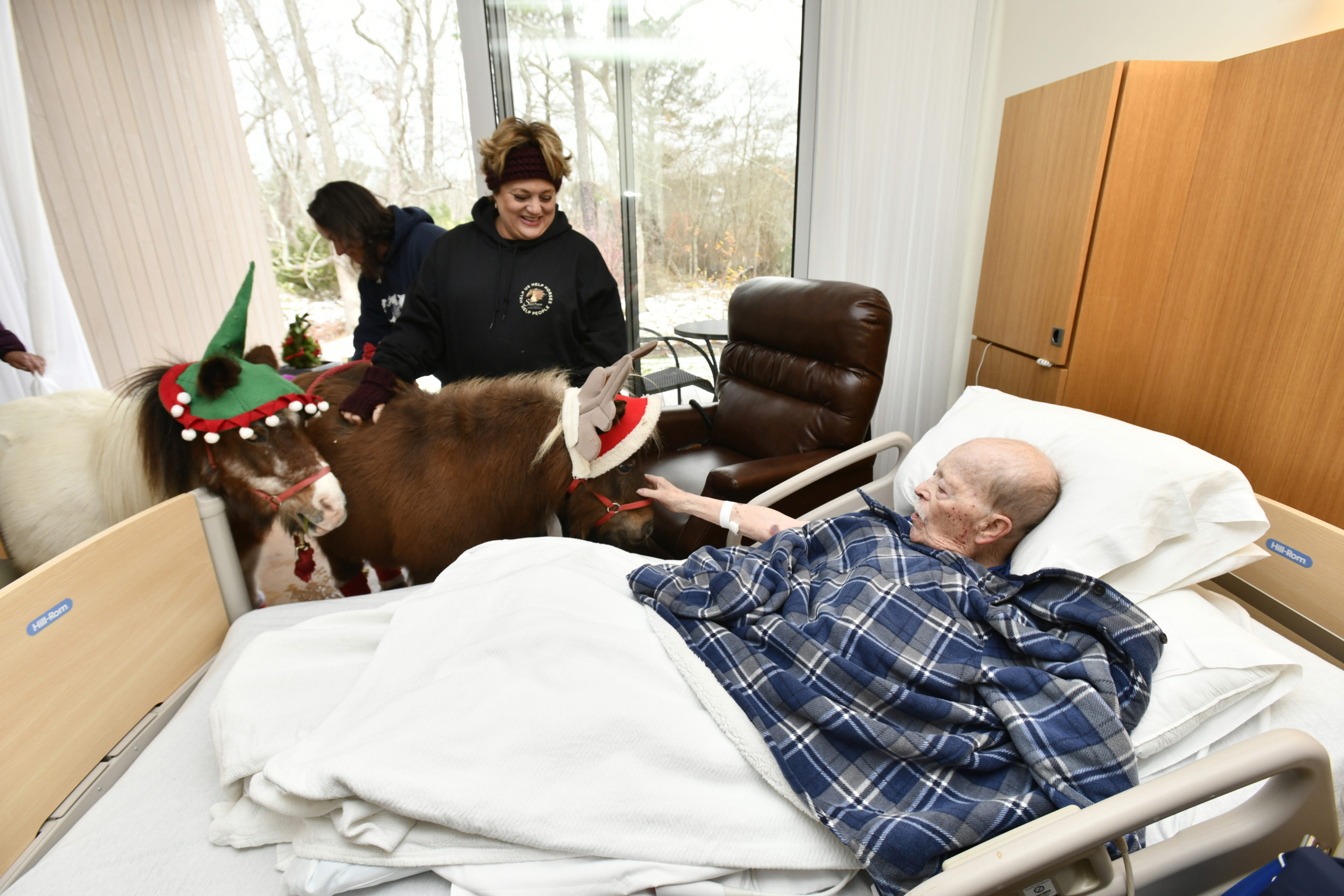 Daniel Byrne gets a visit from mini horses Sweetie and Christmas at the East End Hospice Kanas Center for Hospice Care on Wednesday, December 4.   DANA SHAW