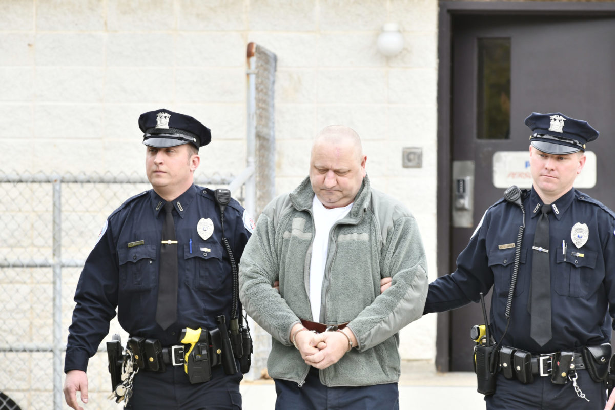 Robert Weis being led to his arraignment by Southampton Town Police in April.  PRESS FILE