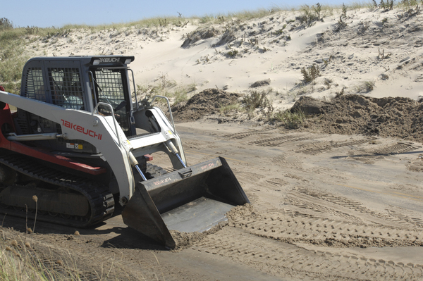 Sand is cleared from Dune Road on Monday near the Inlet where waves washed over the dunes. DANA SHAW
