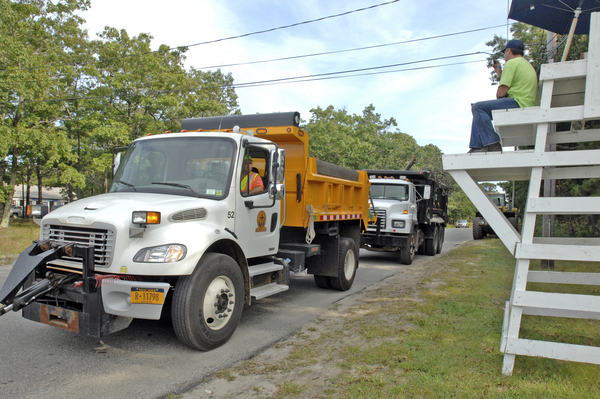 Trucks carrying brush into the Jackson Avenue in Hampton Bays transfer station are counted. The transfer station is staying open later to accept the huge amount of brush coming in.