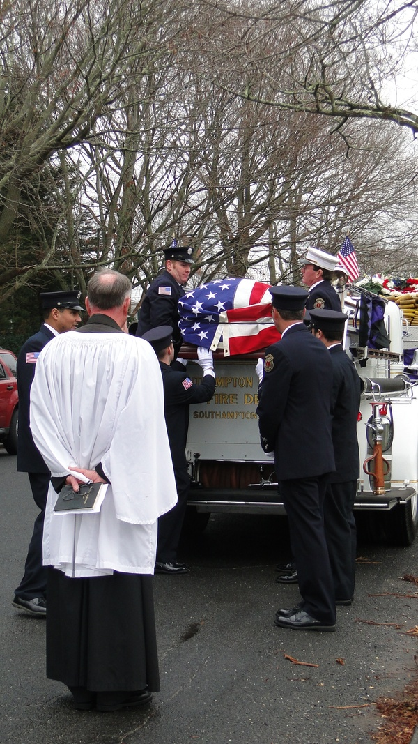 Southampton Fire Department members carry Bill Frankenbach's casket off an Agawam Engine Company truck Saturday morning as Reverend Peter M. Larsen of St. John's Episcopal Church looks on. COLLEEN REYNOLDS