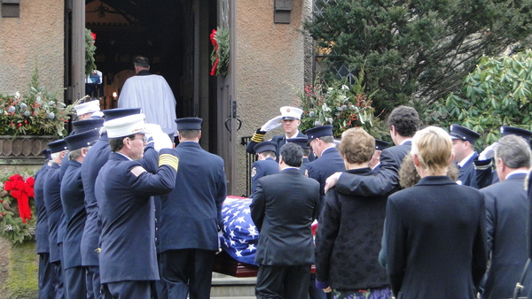 Southampton Fire Department members stand in salute Saturday morning as Bill Frankenbach's flag-draped casket is led into St. John's Episcopal Church in Southampton Village. Mr. Frankenbach's family follows. COLLEEN REYNOLDS