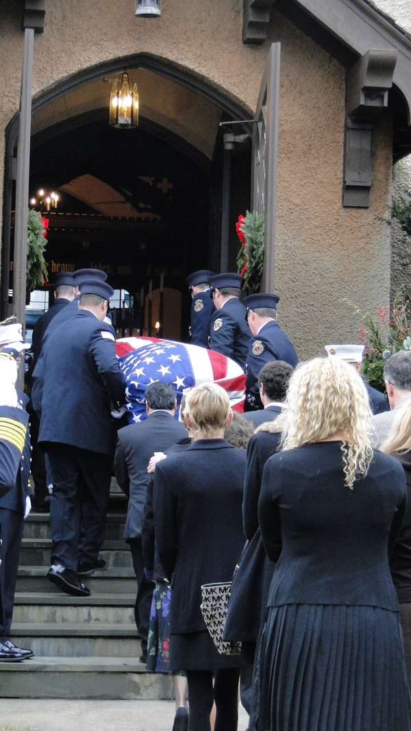 Bill Frankenbach's flag-draped casket is carried into St. John's Episcopal Church in Southampton Village Saturday morning. His relatives follow. COLLEEN REYNOLDS