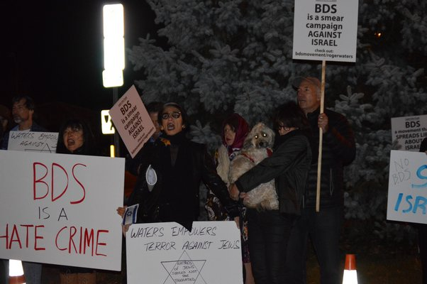 About 60 members of the South Fork community gathered in front of Bay Street Theater on Friday night to protest Roger Waters's performance. ALISHA STEINDECKER