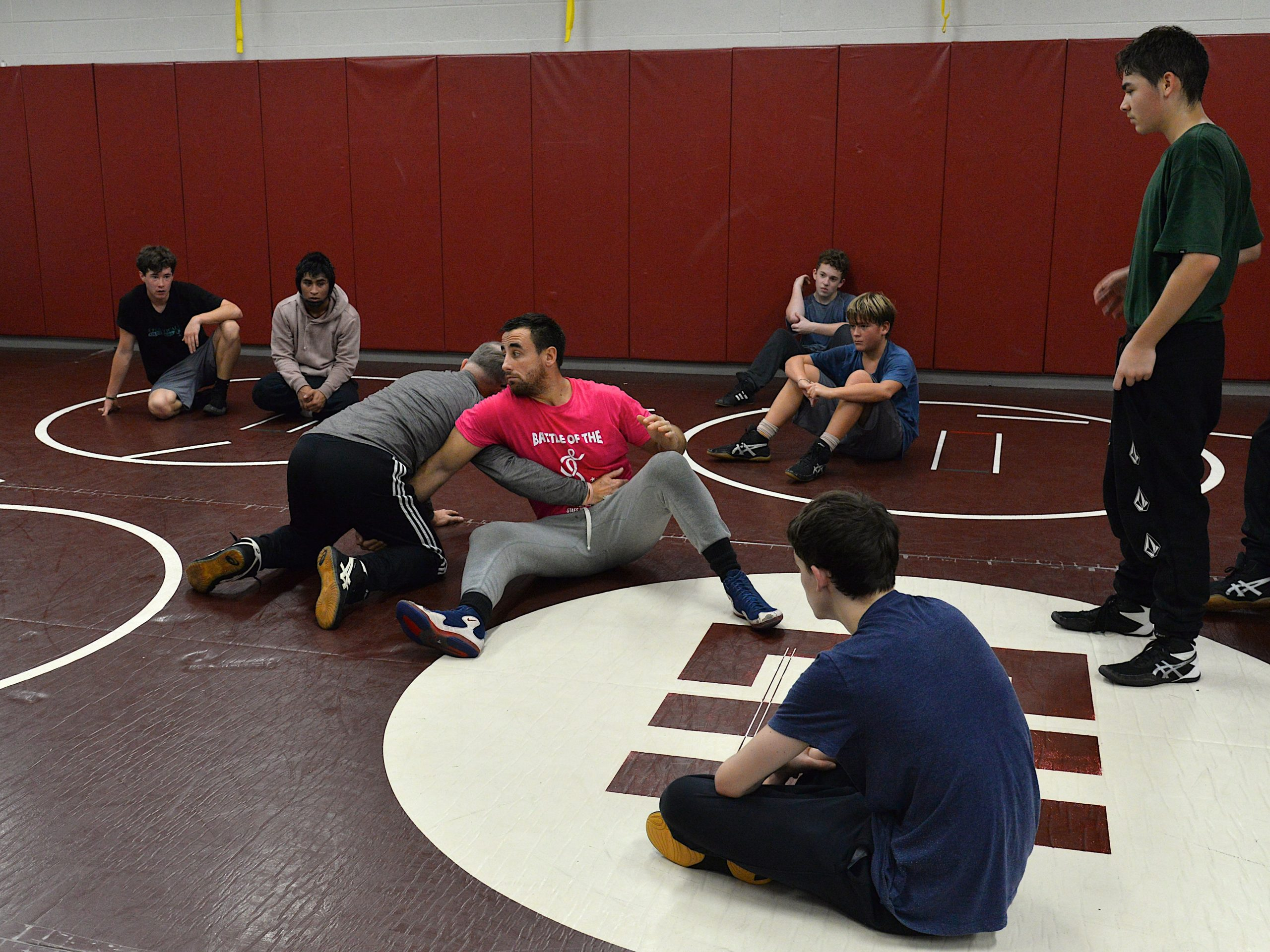 Coaches Ethan Mitchell and Jim Stewart teach their wrestlers during practice.