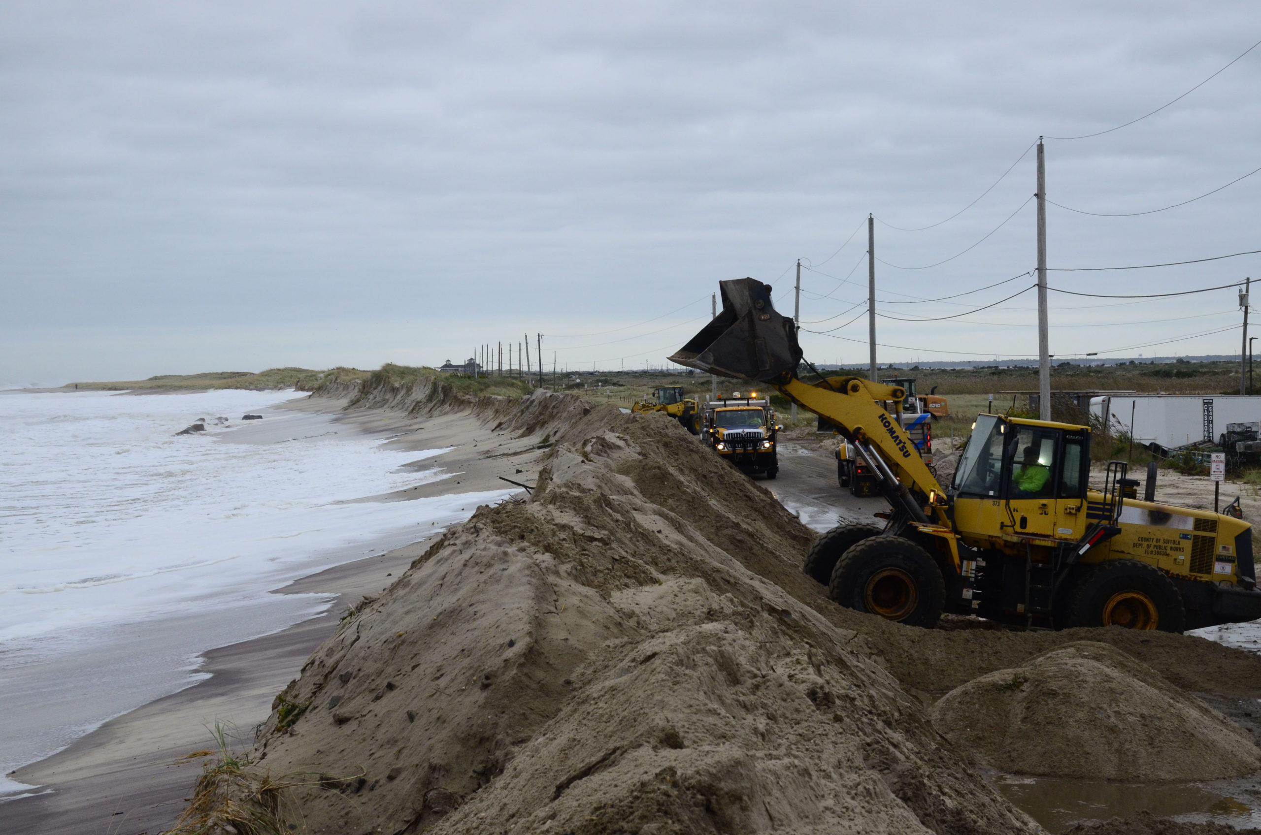 Quick Action Closes Dune Breach October 17 -- Big surf and strong winds from a nor'easter churning in the Atlantic Ocean caused a section of Dune Road near the Shinnecock Commercial Fishing Docks to experience washovers on Thursday night, October 10, prompting local, county and state agencies to pounce into action to bolster the dunes. The washovers were the result of a nearly 100-yard section of dune eroding away with the surf and tides, which were higher than normal during the storm. Last Thursday, Southampton Town Supervisor Jay Schneiderman declared a state of emergency due to severe erosion and the potential of coastal flooding along the eastern end of Dune Road, in anticipation of the nor'easter. The declaration allowed the town to accelerate any required coordination with the State Department of Environmental Conservation to move sand and rebuild the dune. It also allowed the town to request assistance from the Suffolk County Department of Public Works to bring in heavy equipment to reconstruct the dune.