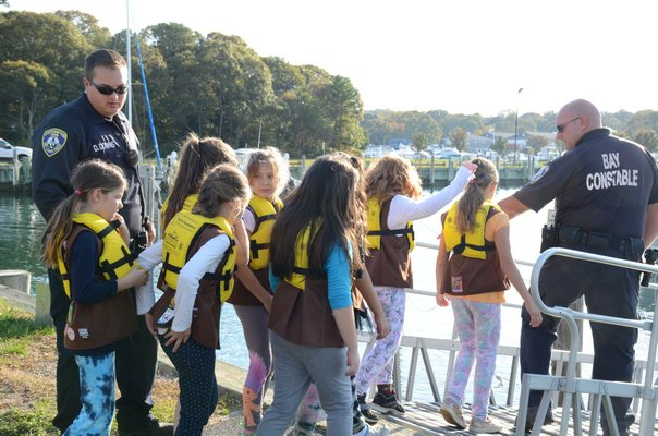 Town of Southampton Bay Constable Rich Franks helps Brownie Troop 759 member Makayla Vignieri put on her life jacket at the Meschutt marina on October 21. GREG WEHNER