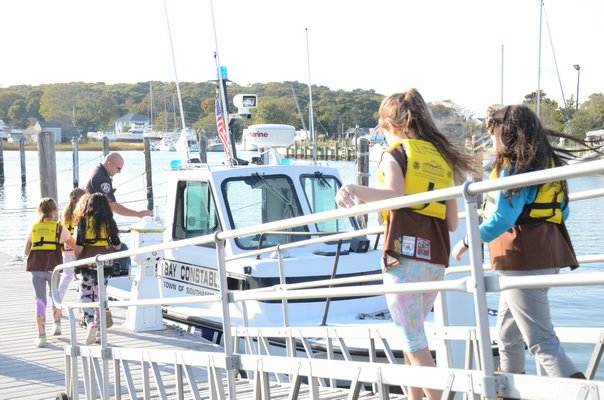 Southampton Bay Constables Donnie Downs (left) and Rich Franks (right) walk members of the Quogue Brownie Troop 759 down a ramp to the dock at Meschutt marina