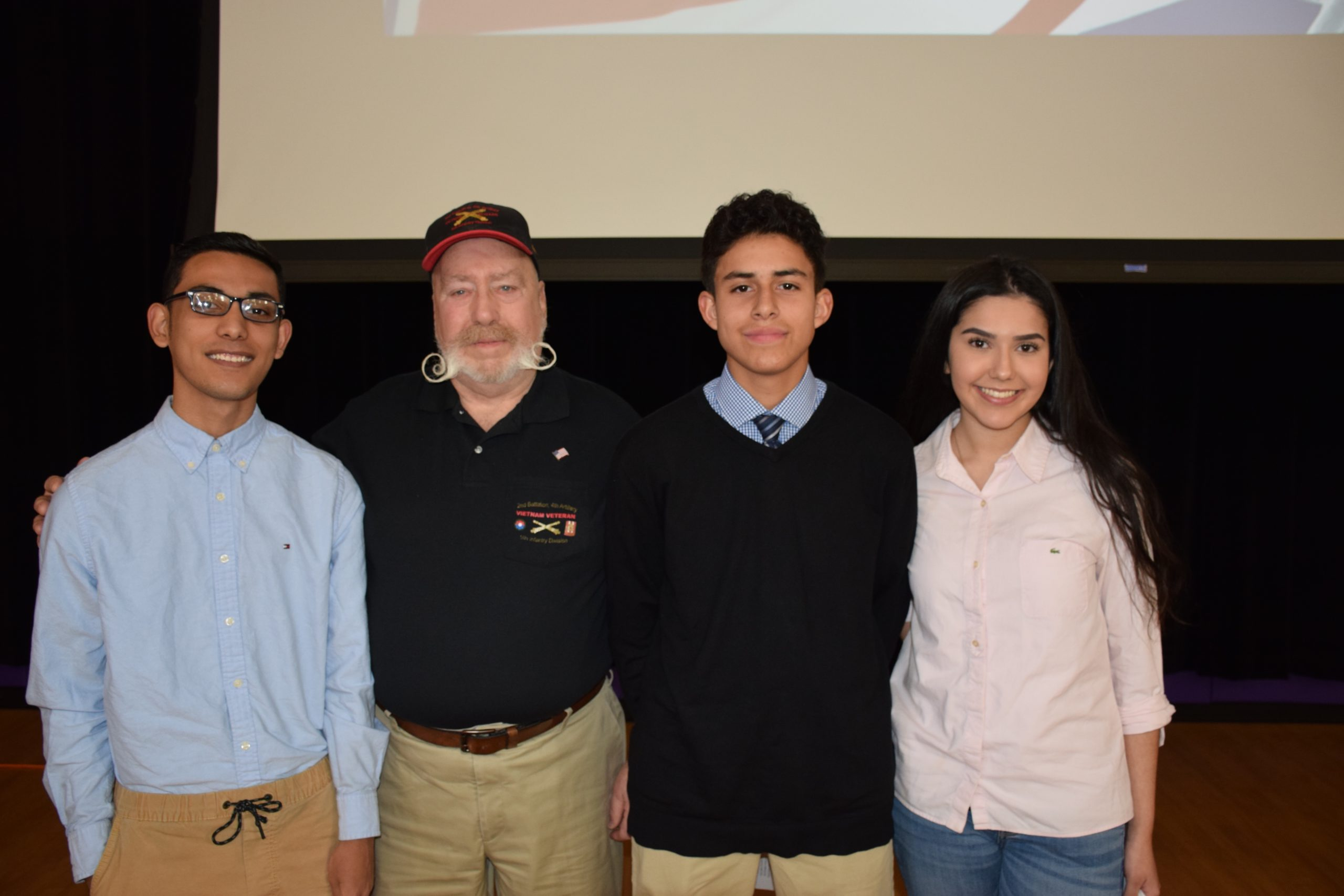 Hampton Bays High School students honored U.S. Navy veteran Dick Crescenzo during a flag ceremony on December 6. Among the students at the ceremony were three students who will be entering the military following graduation. From left, Pedro Robles (U.S. Army), Mr. Crescenzo, Kyle Rodriguez (U.S. Air Force) and Sophia Gonzalez (U.S. Air Force).