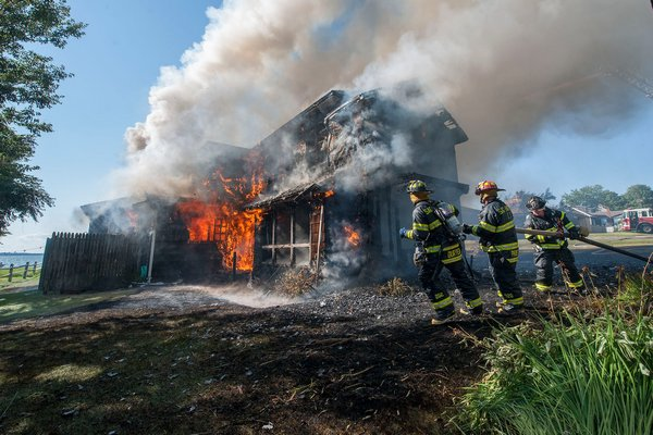 Firefighters work to extinguish a house fire at 13 Peconic Avenue in Northampton Shores on On Thursday