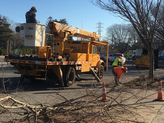 Landscapers were trimming branches of a tree in East Hampton Village on Tuesday morning. ELIZABETH VESPE