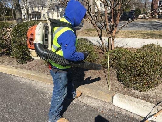 A man using a gas-powered leaf blower.