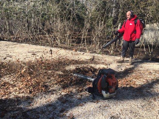 A landscaper using a gas-powered leaf blower.