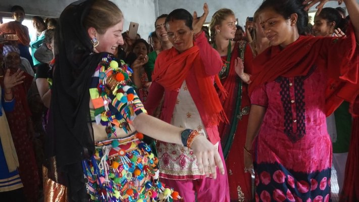 Sophie Flax dancing with some villagers.  COURTESY WILLIAM BARBOUR