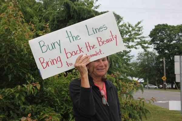 Sharon Adans stands at the corner of Montauk Highway and Eastport-Manor Road on Wednesday to protest the