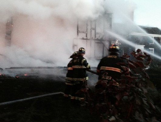 Firefighters battle a blaze in Sagaponack early Monday morning.