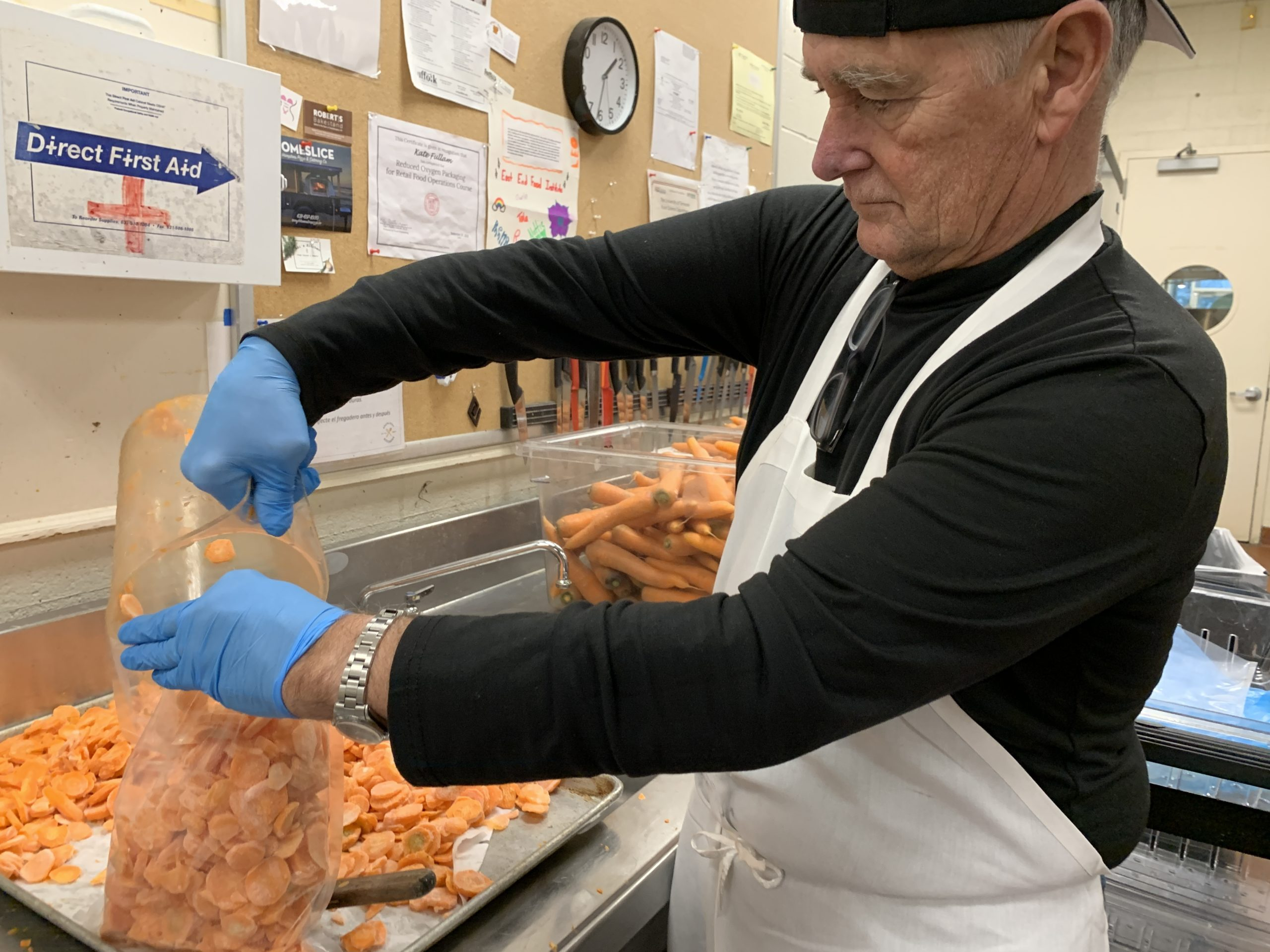 Volunteers helped wash, peel, chop and freeze 1,600 pounds of carrots to be sent to a food bank. Michael Ferran packed the frozen carrots into plastic bags to be vacuum sealed. KIM COVELL