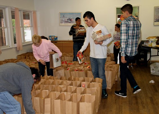 Volunteers pack bags of food for the Thanksgiving holiday at t
