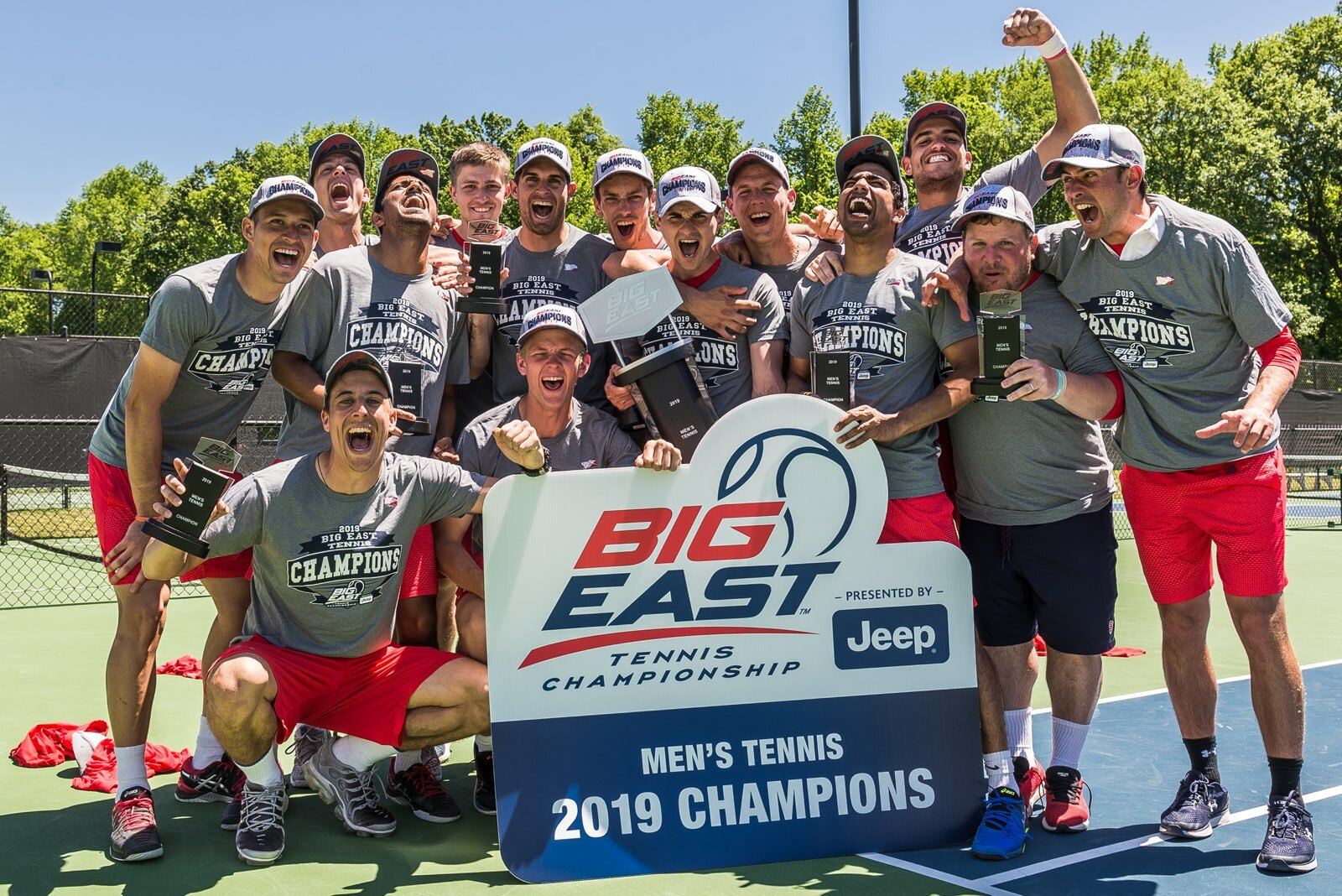 Dillon Pottish, standing directly behind the Big East sign with the Big East Championship trophy, along with Richard Sipala, standing to Pottish's right, helped lead the St. John's men's tennis team this past season as head and assistant coaches.