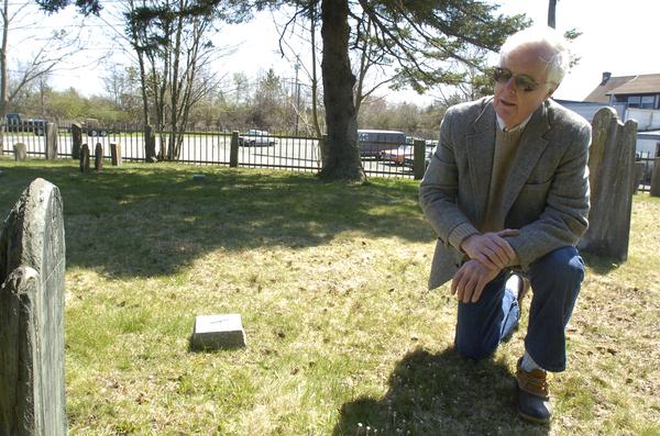 Dr. James Kirkpatrick Flack examines a headstone in the Hayround Cemetery in Bridgehampton.