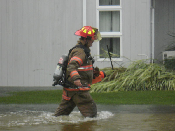 A member of The Westhampton Beach Fire Department wades through flood waters caused by Hurricane Irene. COURTESY WHB FIRE DEPARTMENT