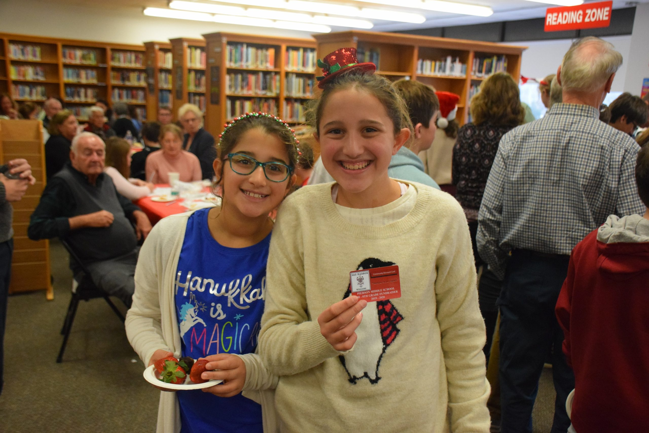 """Pierson Middle School hosted its annual Snowflake Tea on December 13. At the annual event, students in grades six, seven and eight gathered with their grandparents and role models to share schoolwork and projects and kicked off the season with a holiday singalong. Lily and Isabelle Caplin visited local businesses to get their support for the school trip """"rewards card."""""""