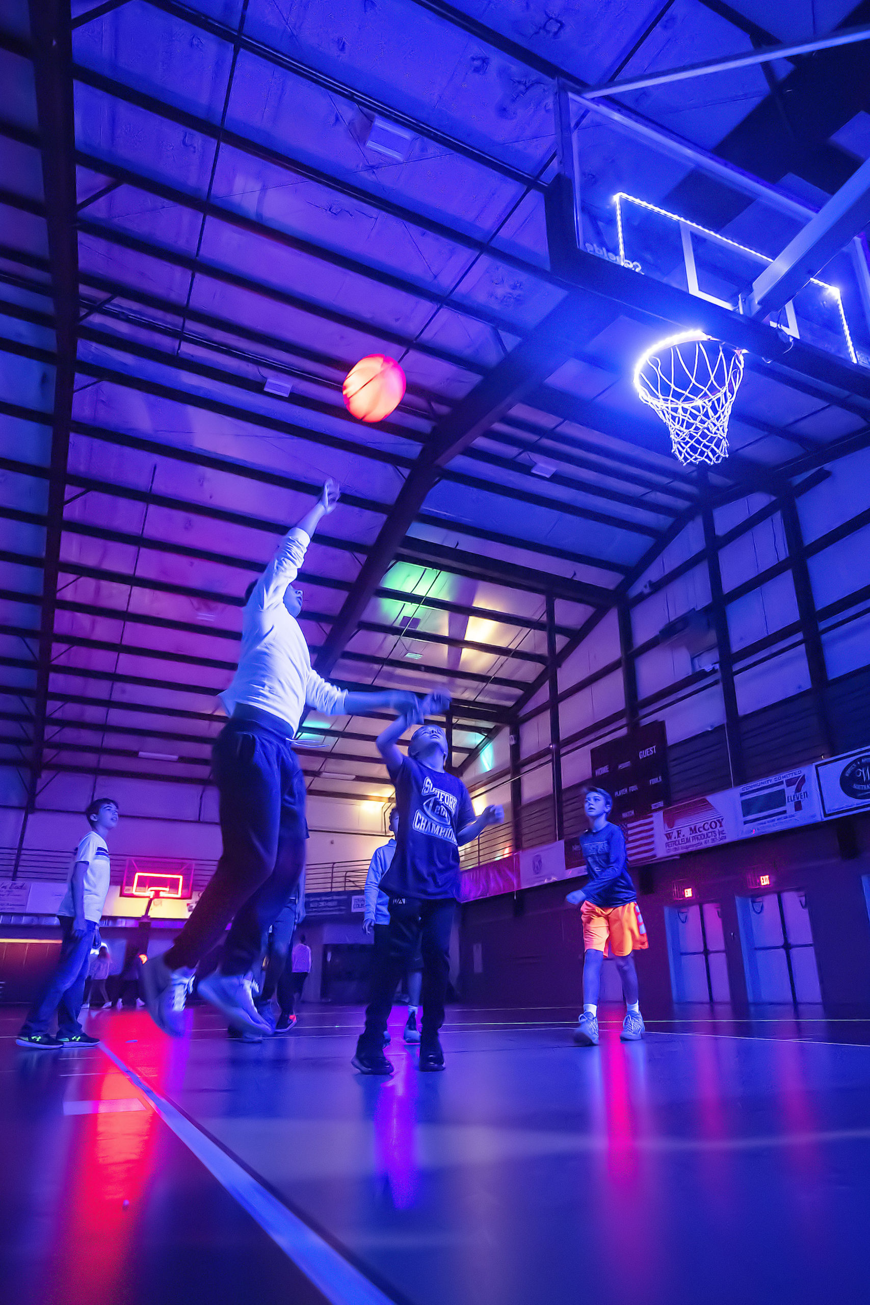 Kids shoot hoops during the Lights Out! Glow Night event at the SYS facility in Southampton on Friday night.  MICHAEL HELLER